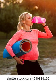 Pregnant woman drinking water after fitness. Thirsty after training expectant lady close-up, free space, sun light flare