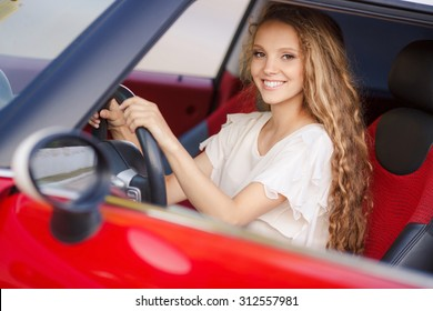 Pregnant Woman Driving a Car. pregnant woman in driving seat of the car. portrait of young beautiful pregnant woman outdoors. smiling pregnant woman sitting in car
