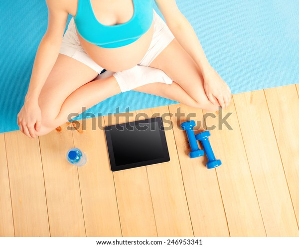 pregnant woman with dumbbells exercising with video course. Overhead of belly, dumbbells, digital tablet  and bottle of water.