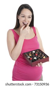 Pregnant woman eating a box of chocolates