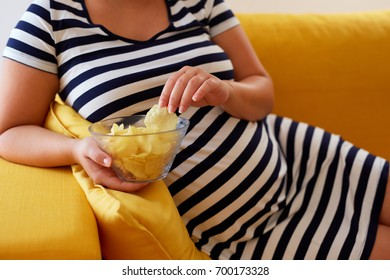 Pregnant woman eats chips while sitting on sofa