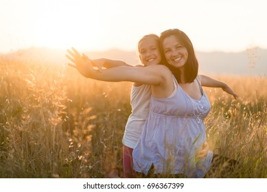 Pregnant woman enjoying summer day with her pretty young daughter