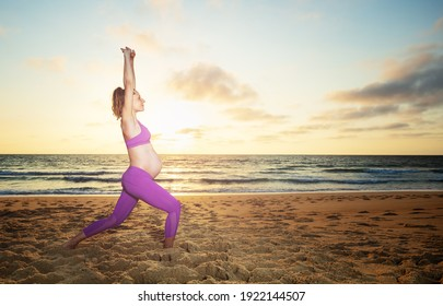 Pregnant woman exercise making sit downs on the sand ocean beach with sunset over water on background