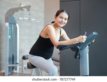 Pregnant woman exercise on the bicycle in sports hall.