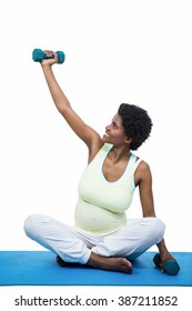 Pregnant woman exercising with dumbbell on white background