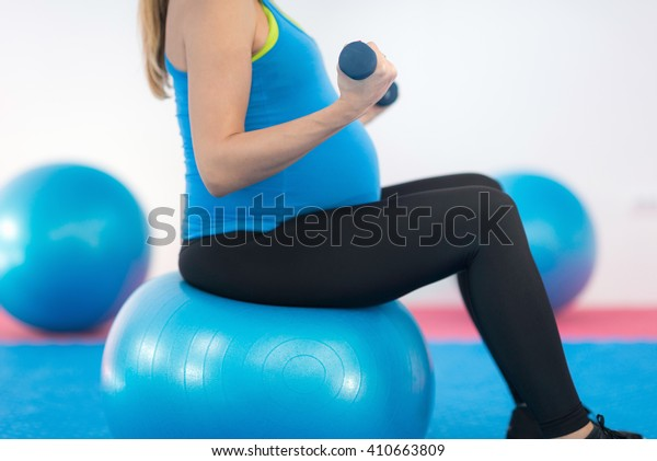Pregnant woman exercising with dumbbell, sitting on fitness ball