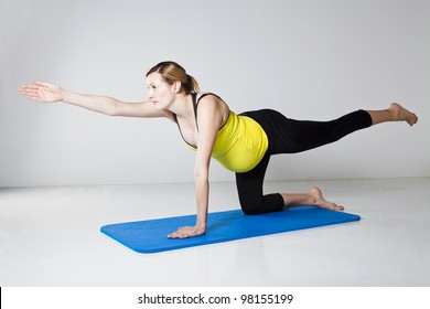 Pregnant woman exercising on mat to develop balance and muscular strength of the core trunk and shoulder muscles