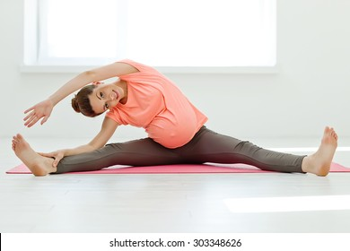 Pregnant woman exercising yoga on the mat