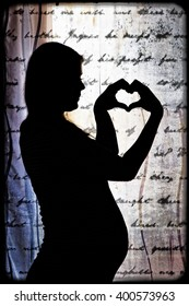 A pregnant woman forming a heart with her hands