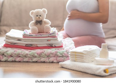 Pregnant woman is getting ready for the maternity hospital, packing baby stuff. pregnant woman preparing and planning baby clothes. Preparing stuff for maternity hospital at home.