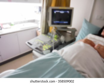 Pregnant woman getting ultrasound in hospital room blur background