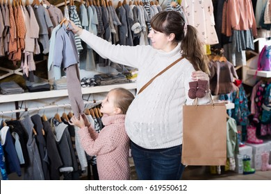 Pregnant woman and girl child choosing childrenâ??s clothes in childrenâ??s store