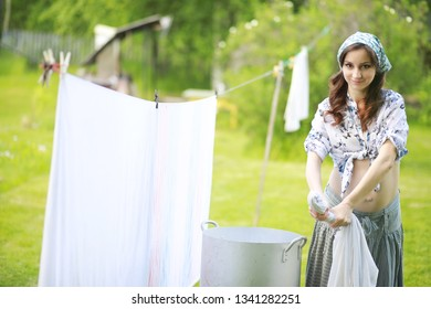 Pregnant woman hanging wash clothes on the rope for drying