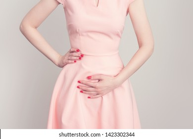 Pregnant woman has a stomach ache, woman touches belly, female hands, cropped image, toned