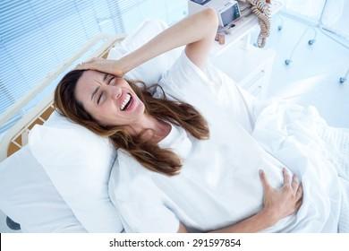 Pregnant woman having birth pangs in hospital room