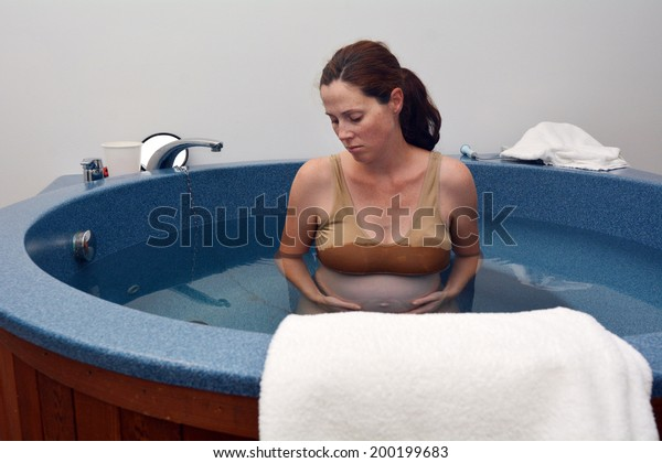 Pregnant woman having contraction during natural water birth. Real life. Real people. Copy space