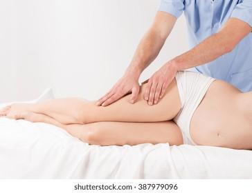 Pregnant woman having professional therapeutic legs massage, white interior.