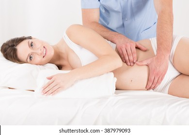 Pregnant woman having professional tummy massage, light interior.