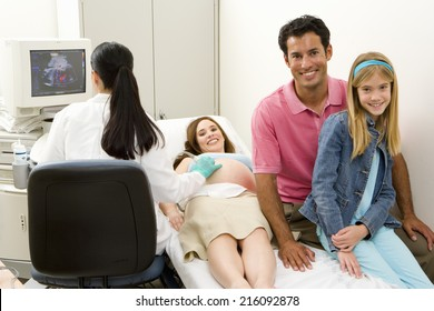 Pregnant woman having ultrasound scan with husband and daughter , smiling, portrait