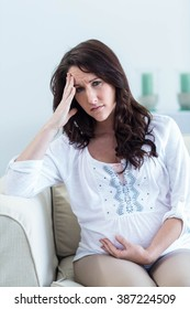 Pregnant woman with headache sitting on sofa