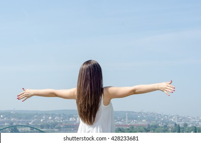 Pregnant woman with her back in a white shirt spreading his arms wide above the city and feel the freedom