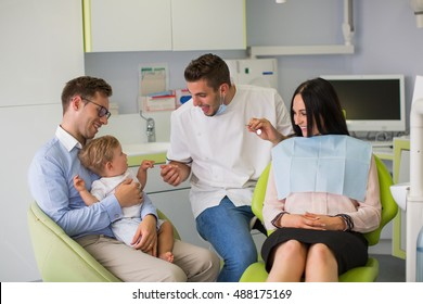 Pregnant woman with her family at dentist before treatment.