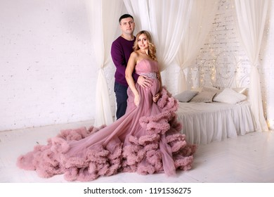 The pregnant woman and her handsome husband stand on the white wall background and  bed