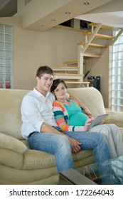 pregnant woman with her husband have fun relax and using tablet comture at modern home