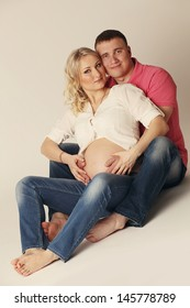 Pregnant woman with her husband posing close together with both of them touching her bare belly with their hands conceptual of family planning and parenting