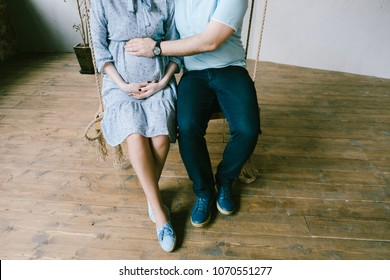 Pregnant woman and her husband sitting on swing and hugging a belly