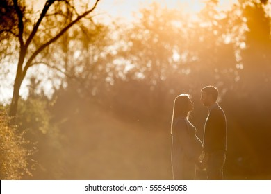 Pregnant woman and her loving man posing at autumn park