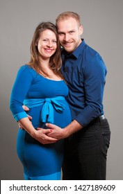 Pregnant Woman and her Man touching the Belly.