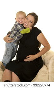 A pregnant woman with her toddler boy, he is giving her a big hug.