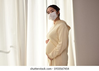 A pregnant woman in her twenties wears a mask for prevention because she is afraid of coronavirus and pollen.