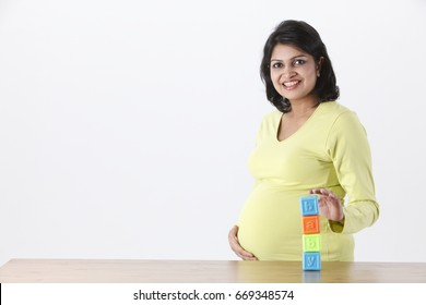 Pregnant woman holding ABC blocks