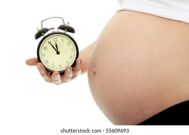 Pregnant woman holding alarm clock isolated in white