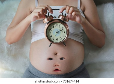 Pregnant woman holding an alarm clock with baby face on tummy sitting on sofa. Waiting baby concept.
