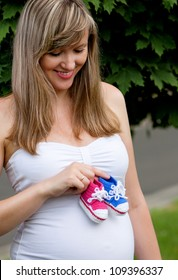 Pregnant woman holding a bootees of baby in different colours in the park outdoors