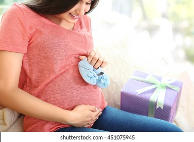 Pregnant woman holding bootees on belly at baby shower party