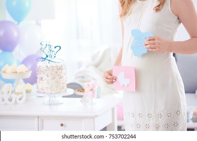 Pregnant woman holding cards for baby shower party, indoors