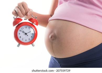 Pregnant woman holding clock