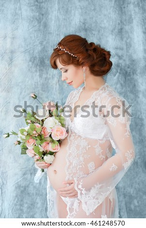 5fed1d95b Pregnant woman holding flowers, standing in the boudoir dress (negligee) on  a blue