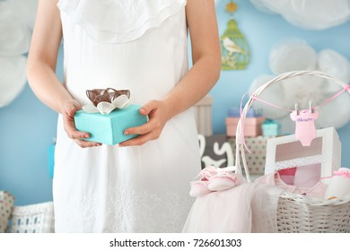 Pregnant woman holding gift at baby shower party indoors