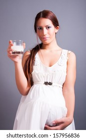 pregnant woman holding glass of milk