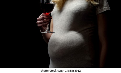 Pregnant woman holding glass of wine, alcohol addiction, unhealthy habit