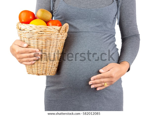 Pregnant Woman holding Orange, tomato, Apples and kiwi. isolated on white background. Health care concept.