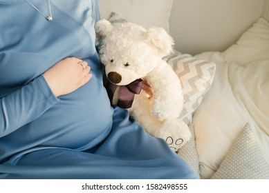 A pregnant woman holds a hand on her stomach and next to it a stuffed bear toy