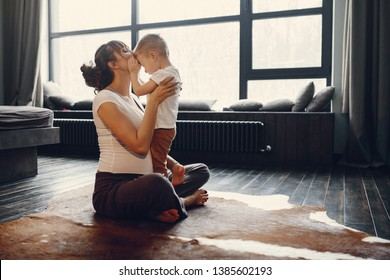 Pregnant woman at home. Mother with son doing yoga. Family in a room with large windows