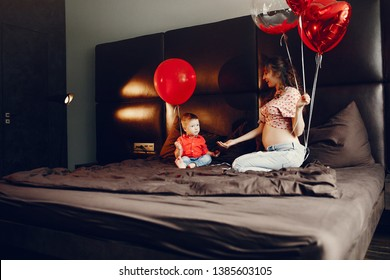 Pregnant woman at home. Mother with son in a bed. Family in a room with decorstions for Valentine's day