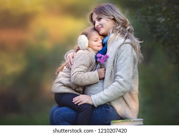 Pregnant woman is hugging and loving her daughter in the autumn park